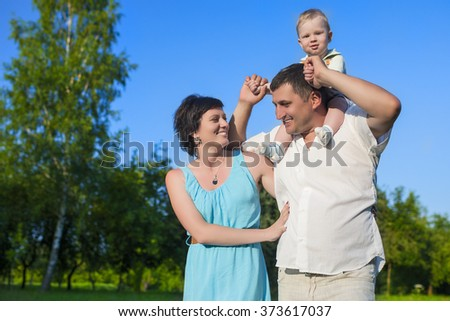 Human Relationships Concepts. Young Caucasian Family of Three People Having Good Time Together Outdoors.Horizontal Image Orientation - stock photo