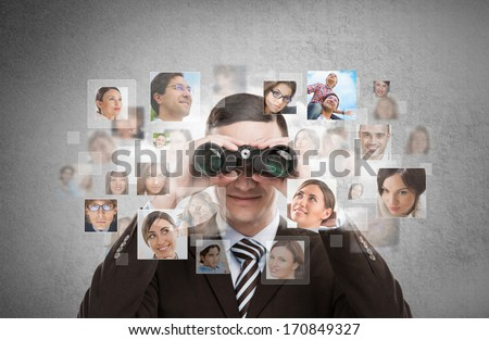 Human resources, CRM, assessment center and social media concept - business man looking for employees through binoculars. Lots of people portraits around him - stock photo