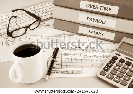 Human resources documents: payroll, salary and employee  time sheets place on office table with cup of coffee and calculator, sepia tone - stock photo