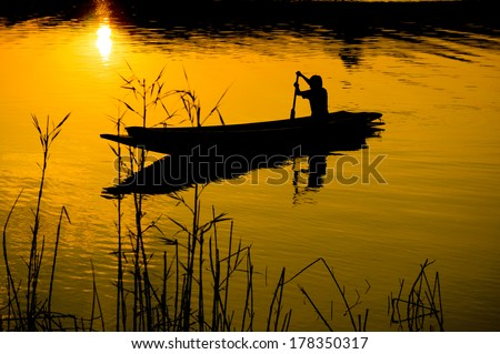 Human rowing on the boat over dramatic sunset, human sailing rowboat - stock photo