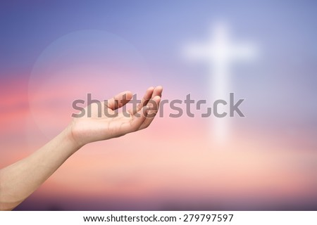 Human's hand pray for cross blurred sky background ,hands isolated on blurred backgrounds. - stock photo