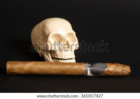 Human scull action smoking cigar on black background - stock photo