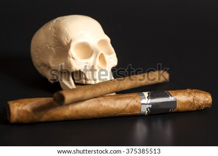 Human scull action smoking cigars on black background - stock photo