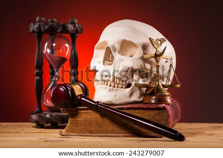 human scull, gavel, scales of justice and old book - stock photo