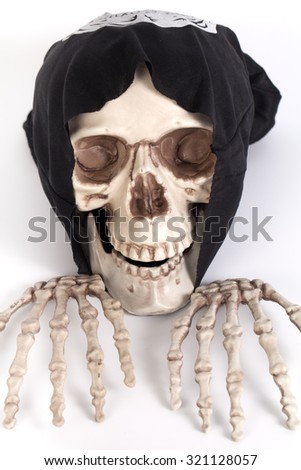 Human Skull and Human Hand with devil black cap - stock photo