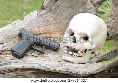 human skull model and gun on log - stock photo