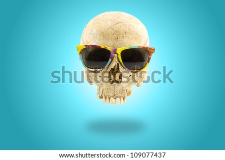 Human skull with colorful sunglasses over light blue gradient background - stock photo