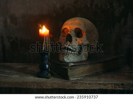 Human skull with old book and lighting candle on dark background - stock photo