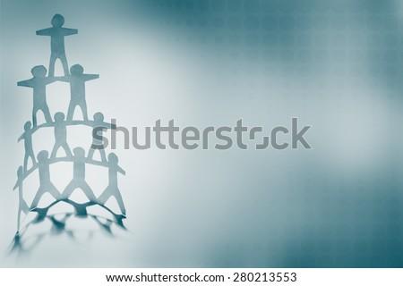 Human team pyramid on blue background - stock photo