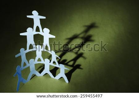 Human team pyramid on green background - stock photo
