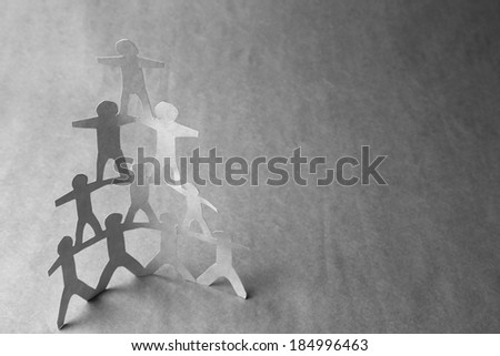 Human team pyramid on grey background - stock photo