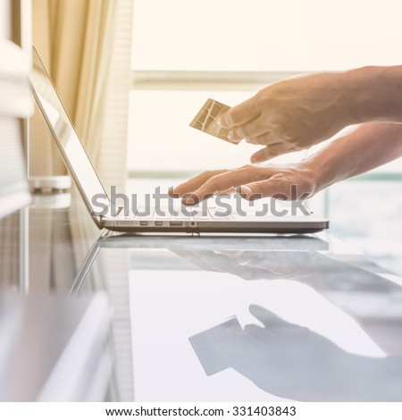 Human woman hand holding credit card while using computer for internet product ordering/ online shopping/ banking tele-booking: Buyer/ customer typing credit card number order goods from home: PPC IM  - stock photo