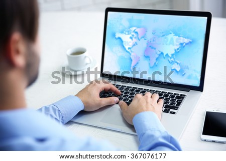 Human working with laptop, with world map and network on screen - stock photo