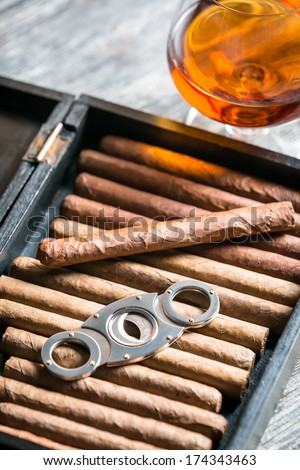 Humidor full of cigars, guillotine and cognac - stock photo