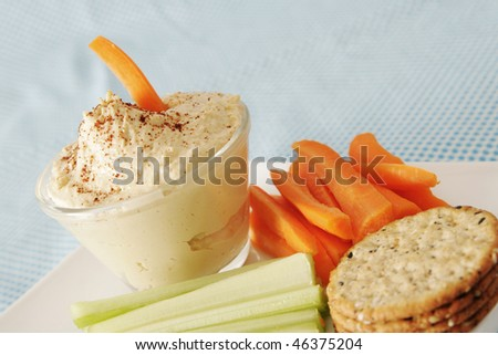 Hummus in a clear bowl with carrot and celery in a white plate - stock photo
