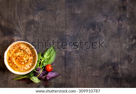 Hummus on a plate with cherry tomatoes and herbs on a dark wooden background. Middle eastern dish. Space for text - stock photo