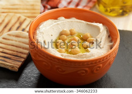 Hummus topped with whole chickpeas, and olive oil - stock photo