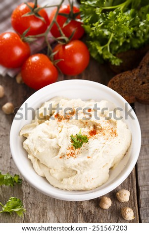 Hummus with vegetables and herbs - stock photo