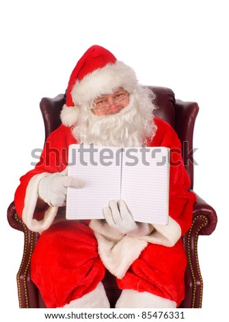 Humorous closeup of Santa Claus (that jolly old elf that  lives at the North Pole) reading and writing in the book of good children - stock photo