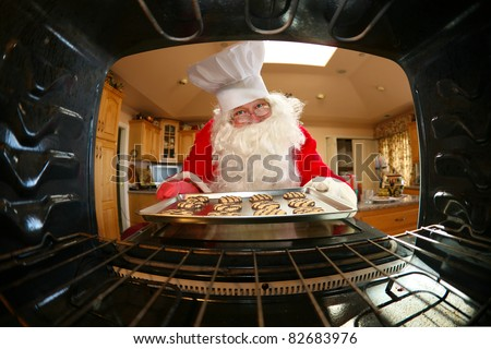 humorous image from within an oven of Santa in kitchen whipping up a batch of cookies, - stock photo