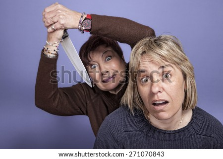 humorous image of a Woman attacked with a knife to a girl from behind - stock photo