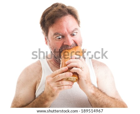 Humorous photo of a scruffy unshaven man in his undershirt, eating a big submarine hoagie sandwich.  Isolated on white.   - stock photo