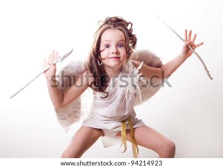 humorous portrait of a cute  six year old girl  dressed as a cupid with white wings, bow and arrow, against studio background - stock photo