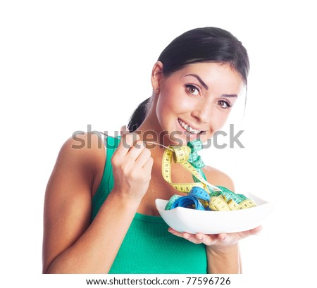 humorous portrait of a young woman keeping a diet and eating measuring tapes - stock photo