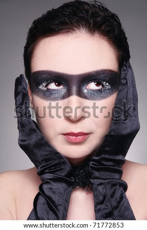 Humorous portrait of young woman with fancy mask painted on her face and thoughtful expression - stock photo