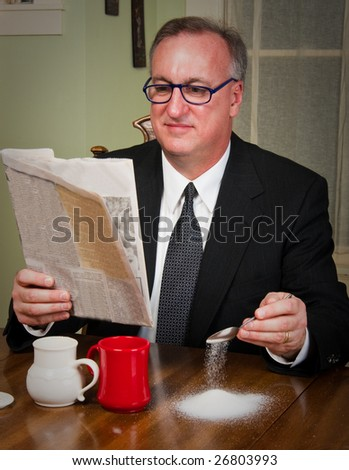 Humorous scene of a business man dressed in a suit and tie sitting down to morning coffee reading the newspaper and absentmindedly missing the cup as he adds sugar to his coffee. - stock photo