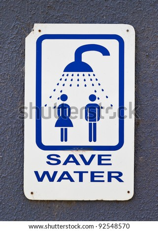 Humorous sign on showering facility advising people to shower together. - stock photo