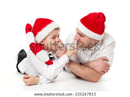 Humour portrait of father man and son boy kid child in Santa's hats, teasing pushing nose to each other - stock photo