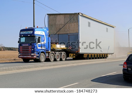 HUMPPILA, FINLAND - MARCH 29, 2014: Truck hauls heating plant as oversize load. Road surveys are necessary, if the dimensions of the exceptional load do not enable traveling on the most direct route. - stock photo