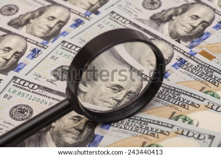 Hundred dollar banknote under magnifying glass - stock photo