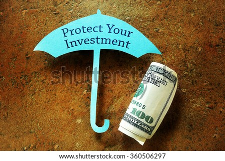 Hundred dollar bill under a paper umbrella with Protect Your Investment text                                - stock photo