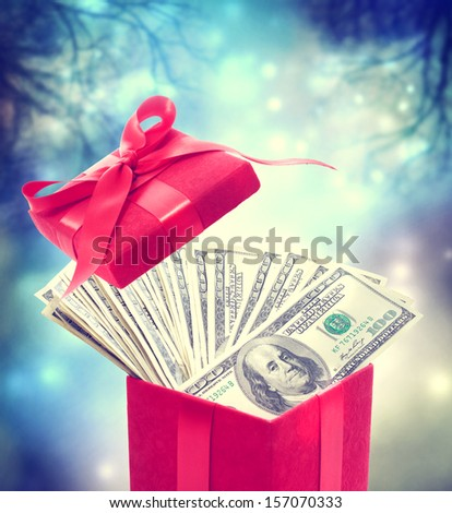 Hundred dollar bills in the red present box at magic night - stock photo