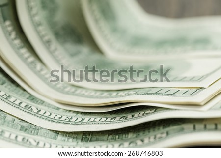 hundred dollar bills on wood table - stock photo