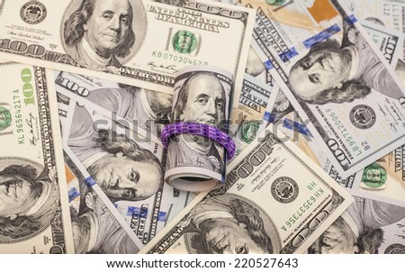 Hundred dollar bills rolled up with rubberband on dollars background  - stock photo