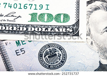 Hundred dollar near seal of Federal Reserve System. Stacked macro photo. - stock photo