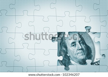 Hundred dollar under puzzle pieces extreme closeup - stock photo