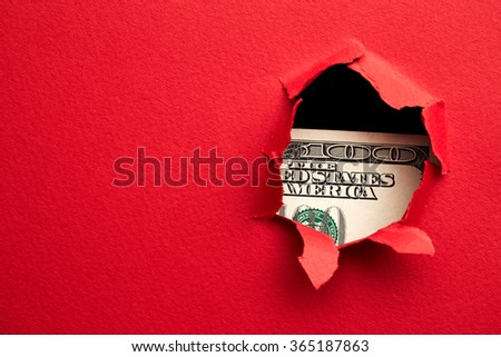 Hundred dollars in hole of red paper - stock photo