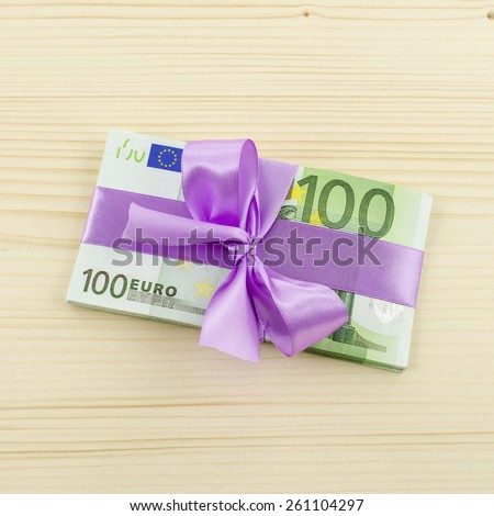 Hundred euro bill with pink bow on wooden table - stock photo