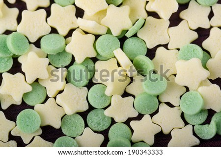 Hundreds and thousands circle and stars cake sprinkles close up on table - stock photo