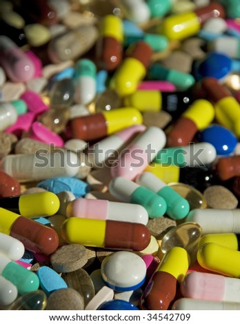 hundreds of assorted pills and capsules receding to BG.  Shallow DOF.  All trademarks removed. - stock photo