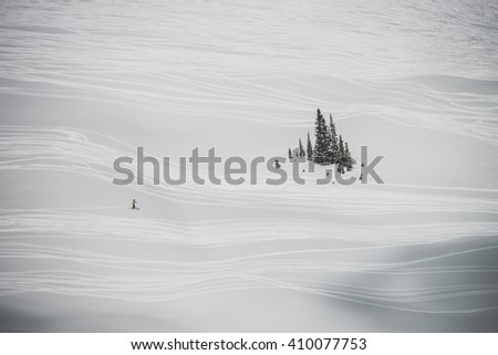 Hundreds of ski tracks making the snow appear abstract from a distance - stock photo