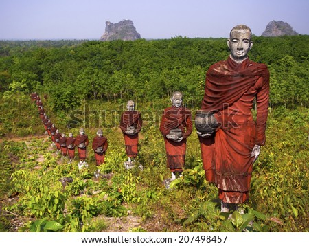 Hundreds of statues of Buddhist monks collecting alms surround the massive Win Sein Taw Ya Buddha, the largest Reclining Buddha image in the world, near Mawlamyine, Myanmar.  - stock photo