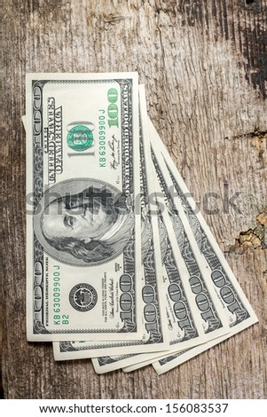 Hundreds of US dollars on old wooden background - stock photo