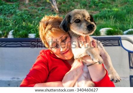 Hunedoara, Romania - 01 July 2014: Happy Blonde Woman Clutching At Chest Newly Adopted Dog In Hunedoara On July 01, 2014 - stock photo