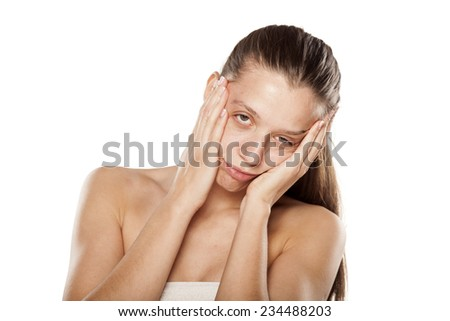 hung young woman touching her face with hands - stock photo