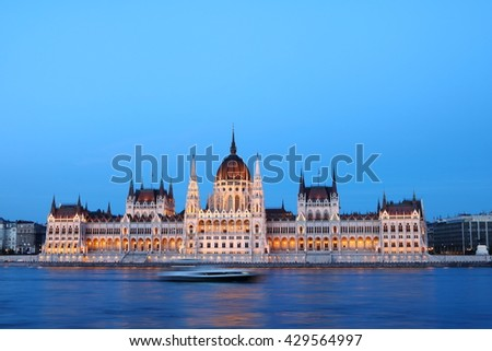 Hungarian Parliament Building illuminated at dusk, along Danube River, with a ship traveling on the river - stock photo